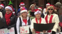 Carolers Protest Tax Bill By Singing Revised Christmas Songs Outside Office of Senator John Cornyn