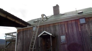 Sweeping the chimney on a slate roof