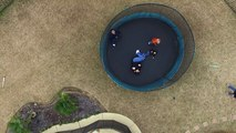 Drone above kids playing on a trampoline.