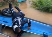 Fijian Police Smash Window of Car Partially Submerged by Floodwaters