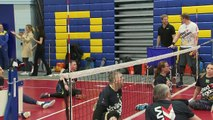 Prince Harry throws a ball in front of Meghan at seated volleyball trials