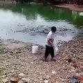 Il vient nourrir les poissons dans son lac... Affamés!