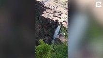 Un homme glisse et tombe du haut d'une chute d'eau