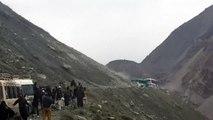 Un bus bloqué sous une pluie de rochers sur une route de montagne