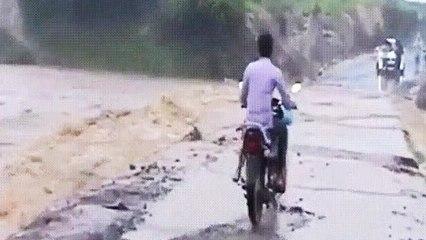 Un motard traverse une route inondée