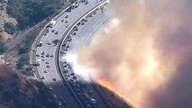 Californie  un hélicoptère largue de leau sur une autoroute au bord des flammes