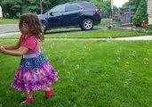 Little Girl Has Fun Chasing Bubbles