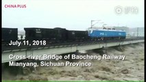 Two fully loaded freight trains were parked on a bridge to keep the bridge stable in a flooded river on Wednesday in Mianyang, Sichuan Province. The flood rec