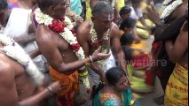 Priest breaks coconuts on devotees' heads during Indian festival