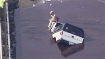 Man sits on car as it is swallowed by sinkhole