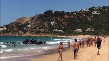 Des migrants en bateau débarquent sur une plage remplie de touristes
