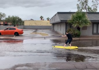 Man Surfs Along Flooded Street in Casa Grande, Arizona