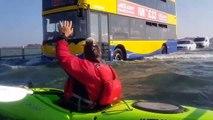 Il fait du kayak sur une route inondée alors que des voitures roulent encore - Mersea Island, Essex