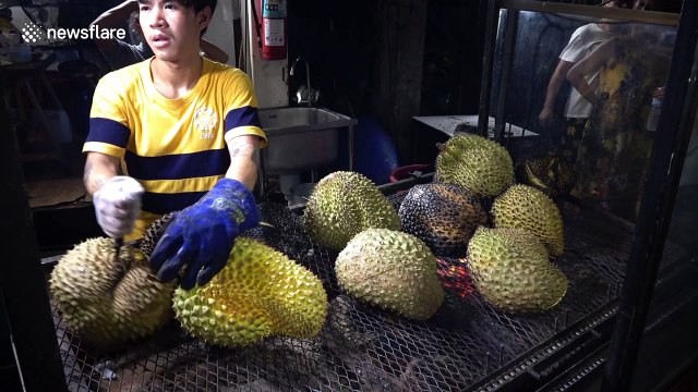 These tourists are eating durian flame-grilled with a blow torch