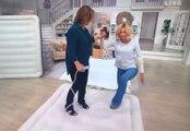 Une présentatrice de télé-achat monte sur un matelas gonflable en chaussures à talons