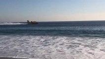 Des canadairs font le plein d'eau dans l'océan en bord de plage en Californie