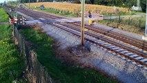 Un cycliste traverse alors qu'un deuxième train arrive au même moment.