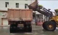 Quand des employés tentent de retirer l'eau d'une route inondée !