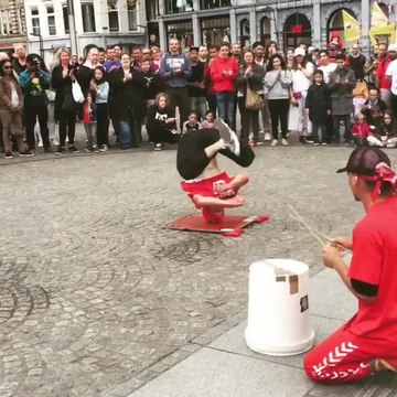 Breakdancer Spins on Head in Front of Crowd on Street