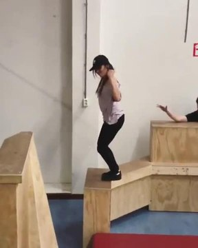Girl Performs Jumps and Flips During Indoor Parkour Training