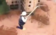 Des ouvriers font du saut à l'élastique sur le chantier pendant la pause déj