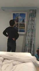 man looks out fake window in ground floor hotel room