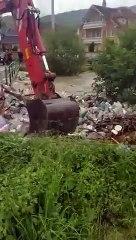 Un employé enlève les déchets accumulés au bord d'une rivière en les envoyant dans la rivière !