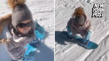 Baby snowboards like a pro with pacifier in mouth