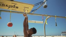 Man Swings Across Beach Obstacle Course