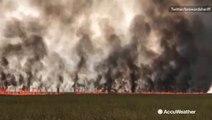 Lightning-sparked brush fire spreads through field