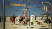Man Works Through Obstacle Course on Monkey Bars at Beach