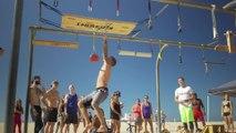 Man Swings Across Peg Board in Beach Obstacle Course