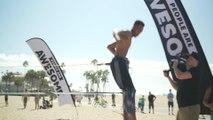 Man Swings Across Slackline Beach Obstacle Course