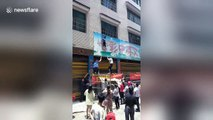 Four-year-old boy hanging from billboard falls down and caught by man in China