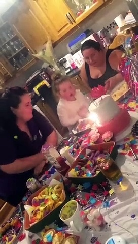 little girl falls off her chair at the table trying to blow out the candles on her birthday cake