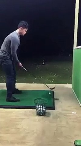 Lad at the driving range accidentally hits the basket of golf balls