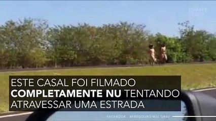 Completamente nu, este casal foi filmado atravessando uma estrada