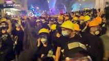 Hong Kong protesters create noise before a police push forces crowds back
