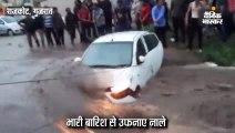 भारी बारिश के कारण बाढ़ के पानी में कार फंसी