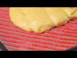 Étalez la pâte rouge sur la plaque. Ensuite, on utilise le racloir pâtissier dentelé.