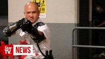 Police officer waves gun at Hong Kong protesters