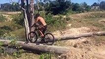 Ce cycliste se rate complètement en traversant une rivière en vélo sur un tronc d'arbre...