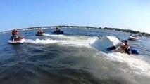 Des baigneurs utilisent des jet skis pour retourner un bateau chaviré