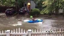 Il fait du kayak dans une rue inondée