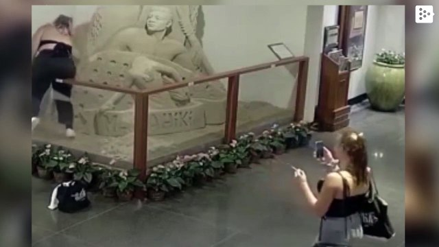 A teenage girl destroys a sand sculpture in a Hawaii hotel