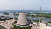 Cette pelleteuse se retrouve à 200m de haut pour démolir la cheminée de ce réacteur