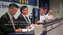 Hong Kong journalists wear masks at a police press conference