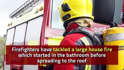 Firefighters tackle large house fire as flames spread to the roof