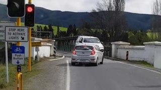 Instant karma pour un automobiliste qui grille un feu rouge pour passer sur un pont à une voie