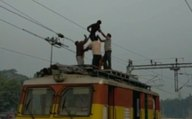 Youth creates high voltage drama holding overhead train wires : Watch Video | OneIndia News